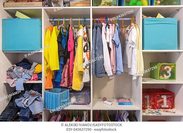 Open wardrobe with things and toys in the children's room
