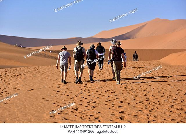 Tourists on foot on the way through the dunes to Dead Vlei, taken on 01.03.2019. The Dead Vlei is a dry, surrounded by tall dune clay pan with numerous dead...