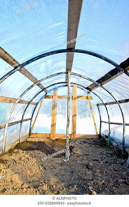 Homemade plastic arch empty greenhouse in winter, view inside