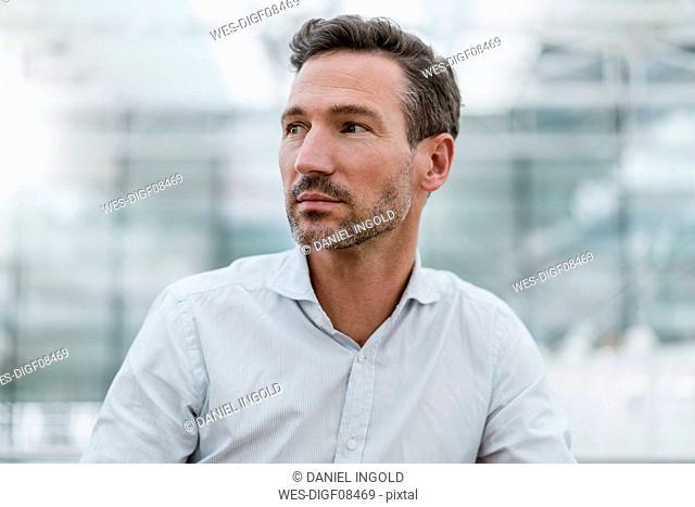 Portrait of confident businessman looking around