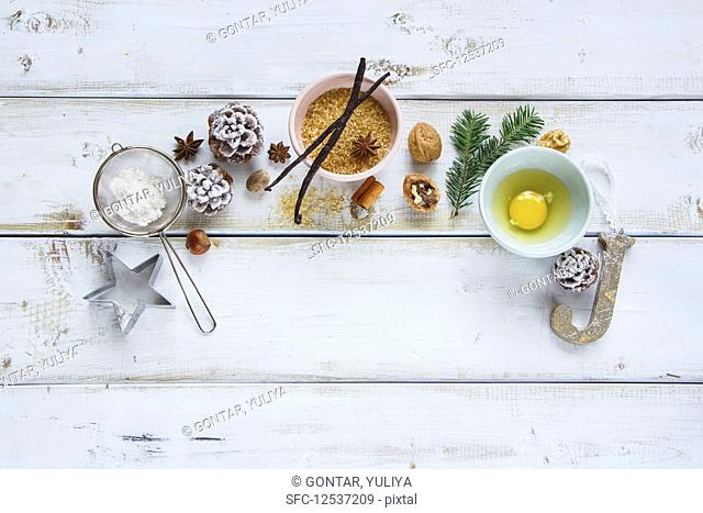 Christmas baking frame made of sugar, egg, flour, larch branch, pine cones, vanilla sticks, anise star and nuts