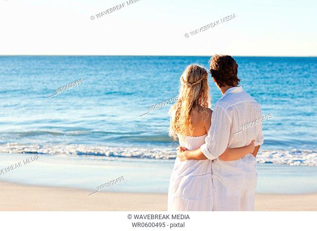 Back view of couple standing at the beach