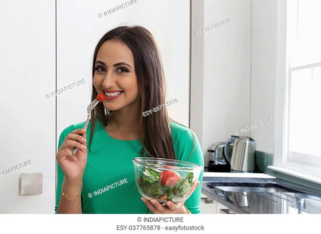 Close-up of a smiling woman eating vegetable salad