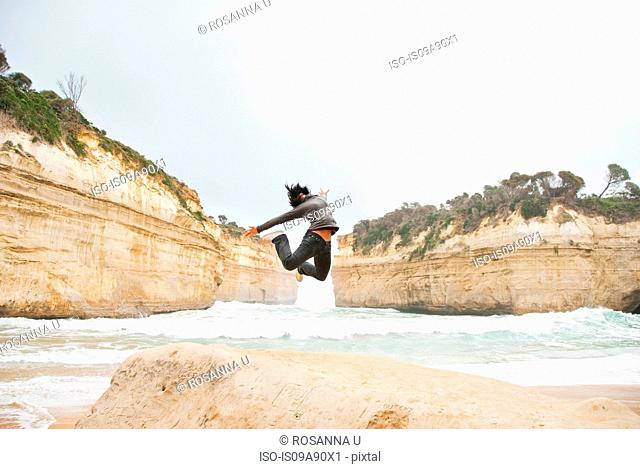 Young woman jumping by Loch Ard Gorge, Melbourne, Australia