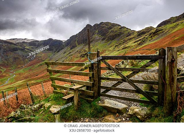 A style and gate on the path to Hay Stacks with Hay Stacks beyond. Lake District National Park, Cumbria, England