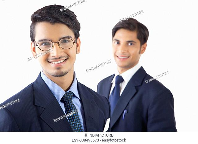 Two smiling young professional men standing against white background