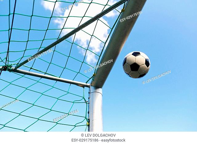 sport, soccer and game - ball flying into football goal net over blue sky