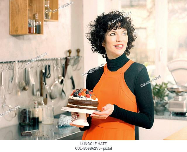 Woman holding chocolate cake decorated with fresh summer fruits