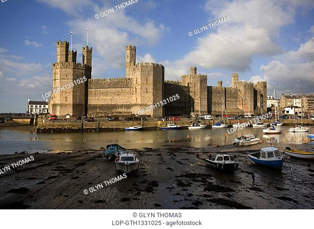 Wales, Gwynedd, Caernarfon, Caernarfon Castle at the mouth of the Seiont river. The castle was begun in 1283 by Edward l as a military stronghold