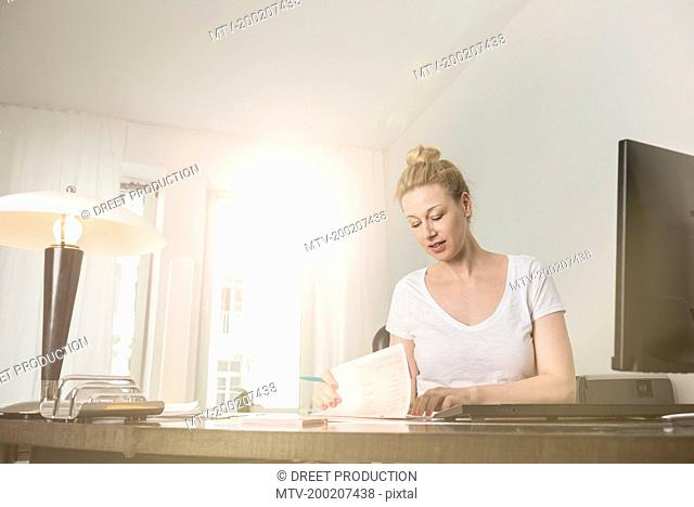 Female receptionist checking out medical records in hospital, Munich, Bavaria, Germany
