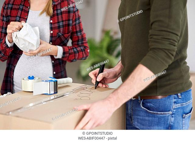 Couple moving house packing and labelling cardboard boxes