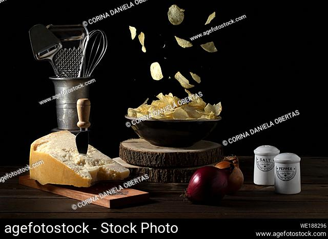 Potato chips falling in a bowl on a table with parmesan cheese, onions, salt and pepper - Dark mood