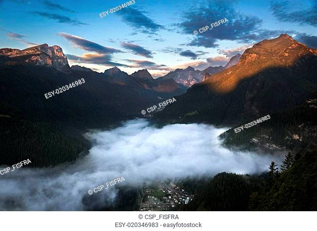 Valley in Dolomites with early morning clouds, Alps, Italy