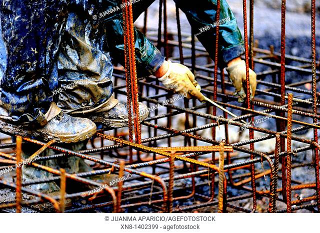 High-contrast image of a construction worker manipulating a rebar structure