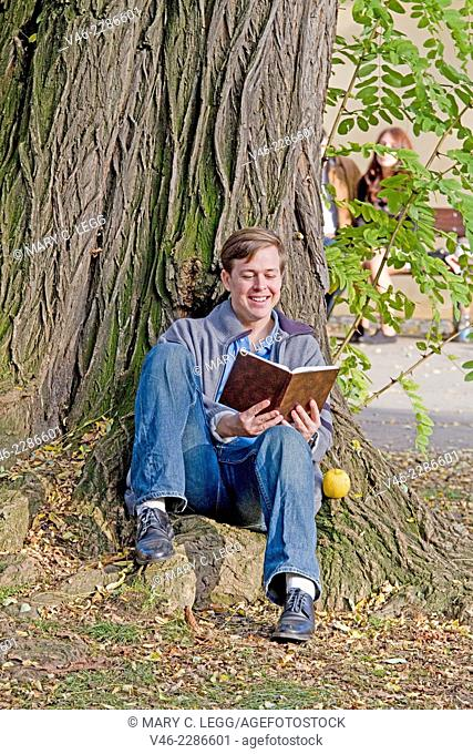Young man with book sitting under a large tee in a park
