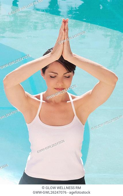 Woman in prayer position at the poolside