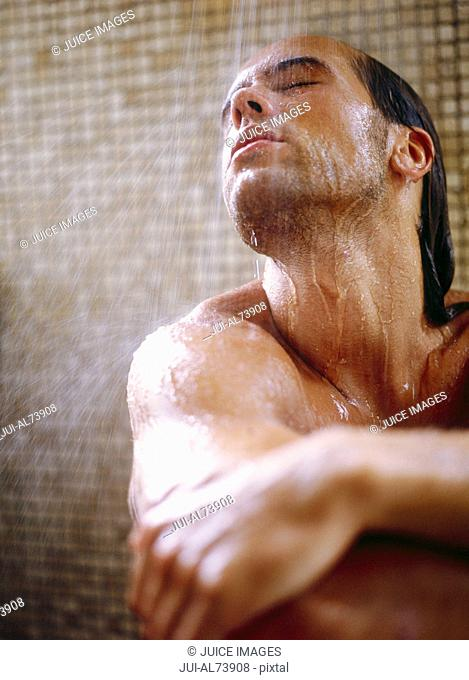 View of a young man sitting down in the shower