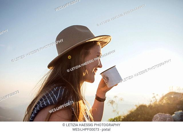 Happy young woman on a hiking trip at sunrise holding a cup