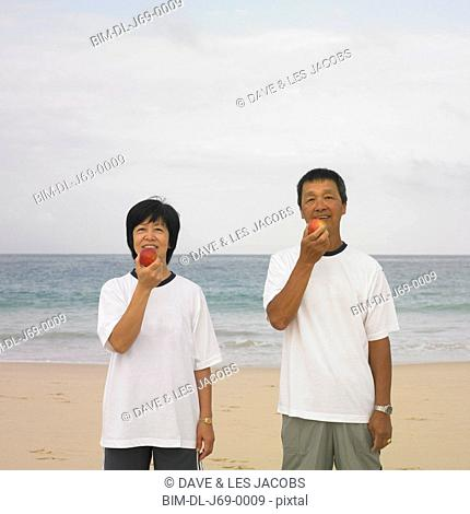 Couple eating fruit at beach