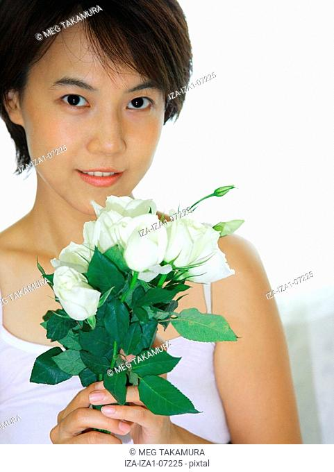 Portrait of a young woman holding a bunch of Roses and smiling