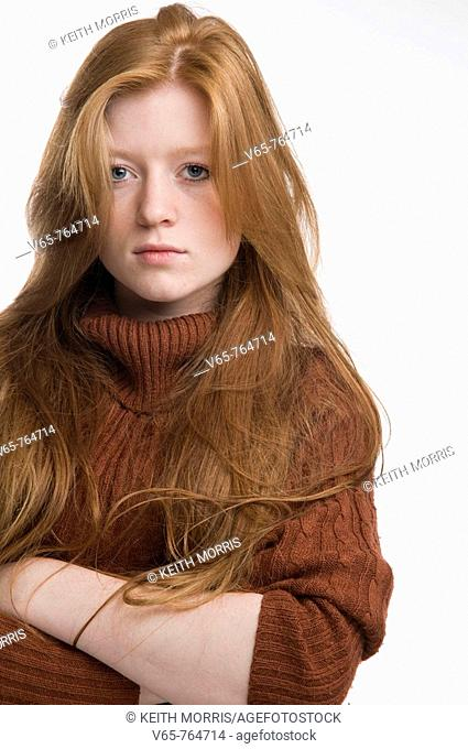 Red haired teenage girl looking moody, arms crossed, staring at the camera. portrait