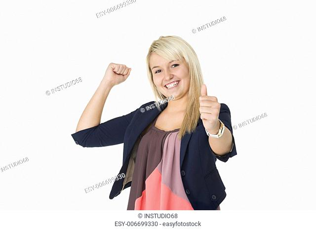 Beautiful elated woman giving a victorious thumbs up and punching the air with her fist in jubilation