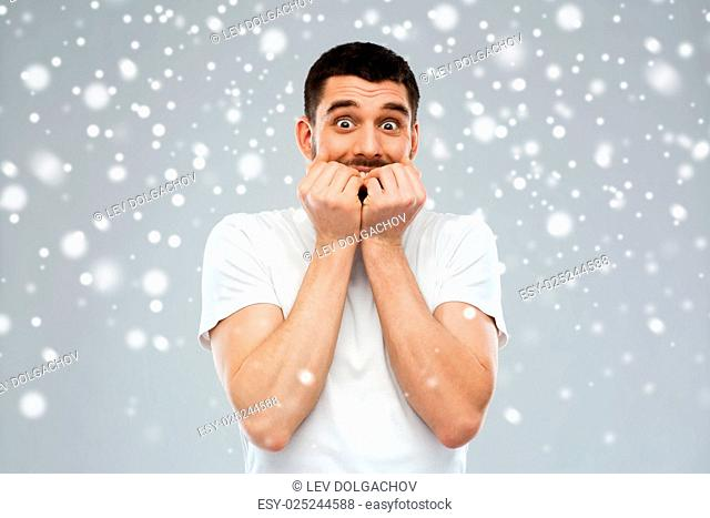 emotion, fear, winter, christmas and people concept - scared man in white t-shirt over snow on gray background