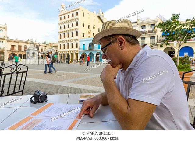 Cuba, Havana, Tourist sitting in pavement cafe, looking to menu card