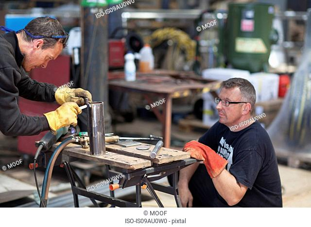 Workers using blow torch in shipyard workshop
