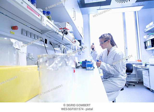 Young female scientist working at biological laboratory filling samples