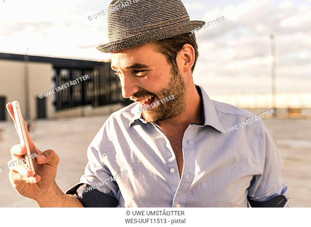 Happy young man with cell phone on rooftop