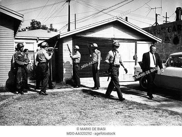 US Police in action. Armed policemen and members of the US National Guard surrounding the house of a weapon dealer during race riots