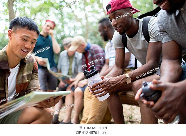 Men friends looking at hiking map in woods