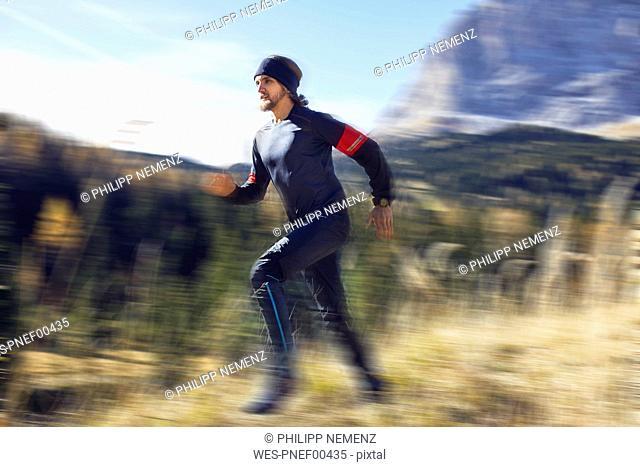 Man running fast on mountain trail