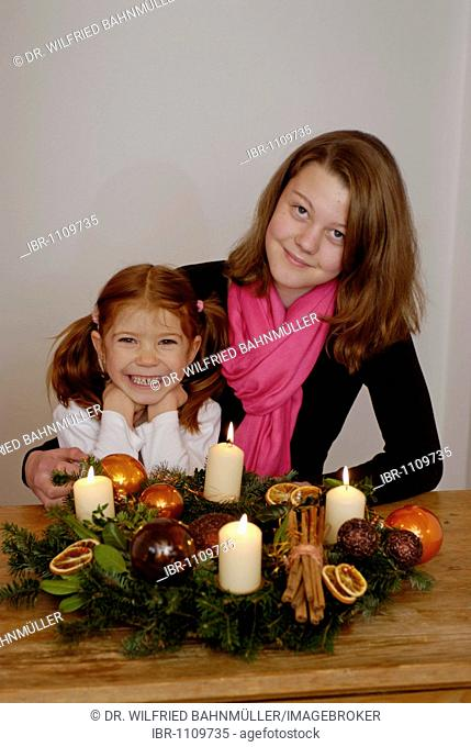 Young woman with child sitting at an advent wreath