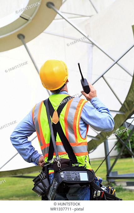 Communications engineer using walkie-talkie at satellite antenna facility