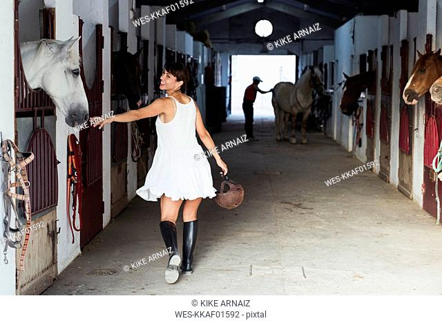 Smiling woman with riding helmet walking in stable