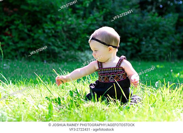 Baby girl at roughly 6 months old outdoors in a natural setting with available light for a lifestyle portrait