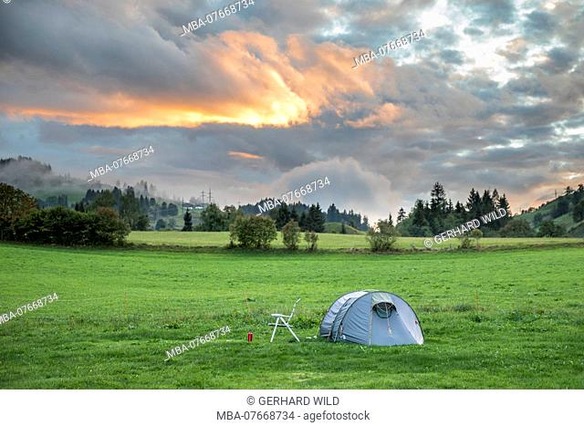 Tent on a meadow before cloudy sky, evening scene, near Embach, Salzburg state, Austria