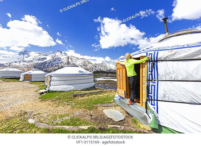A girl stretches and breathes fresh air out of Mongolian tent. Alp Flix, Sur, Surses, Parc Ela, Region of Albula, Canton of Graubünden, Switzerland, Europe
