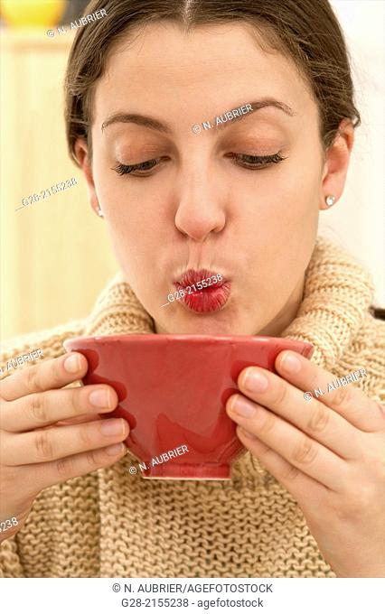 young beautiful woman drinking and blowing to cool a hot drink from a red china bowl, in a beige pull over