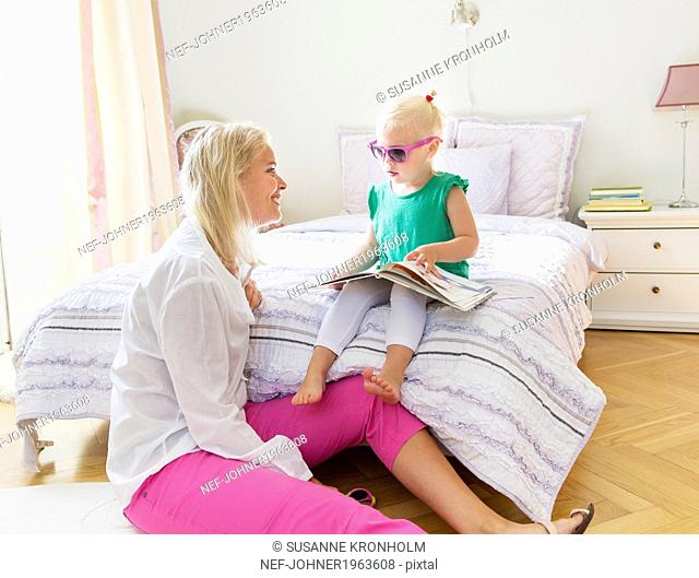 Mother with daughter sitting in bedroom