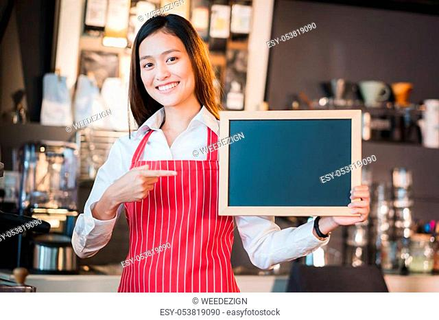 Asian female barista wear red apron point at blank blackboard coffee menu at counter bar with smile face, cafe service concept, Leave space for adding your text