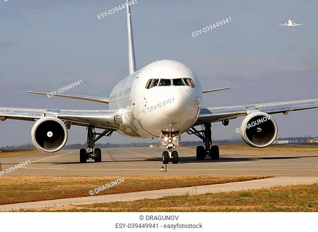 White passenger jet taxiing along the runway