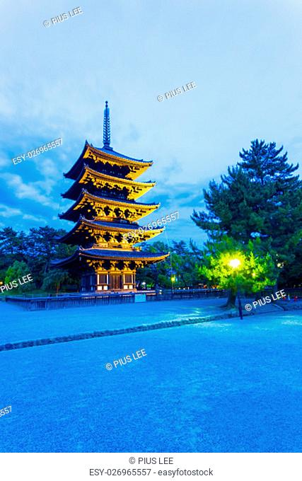 Dramatic blue sky and lighted five story pagoda, goju-no-to, at evening blue hour in Kofuku-ji temple complex in historic Nara, Japan. Vertical