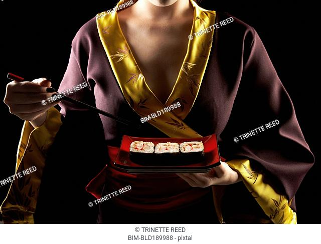 Woman in traditional Asian clothing eating sushi