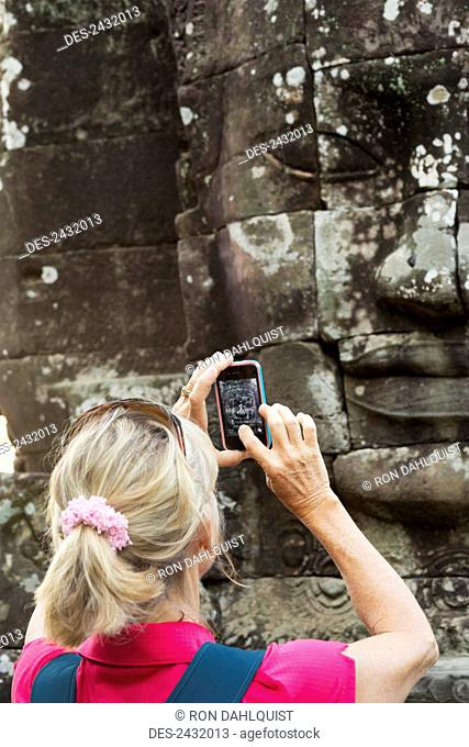 Woman taking picture with iphone of smiling face statue at Bayon Temple in Angkor Thom, near Angkor Wat; Siem Reap, Cambodia