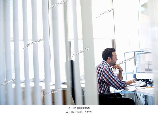 A man working in an office, focusing on a task. Using a computer keyboard and screen