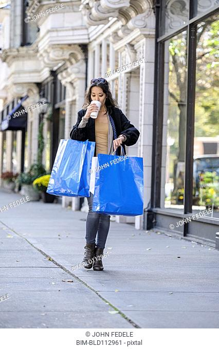 Mixed race woman carrying shopping bags and drinking coffee