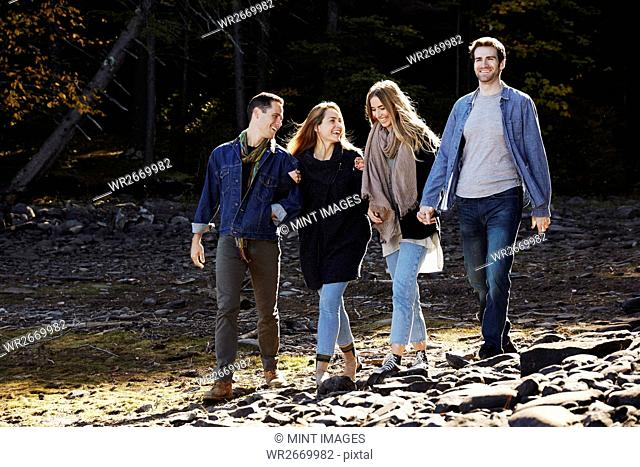 Four people walking along, couples hand in hand, on the shore of a lake